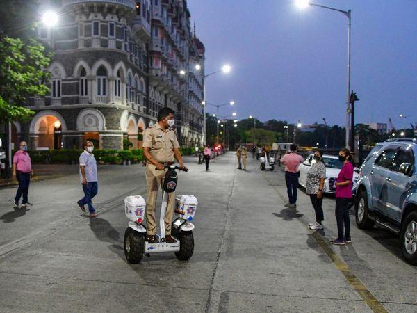 પોલીસકર્મી તાજ હોટલની બહાર ચાલતા લોકોને હટાવી રહ્યા છે.