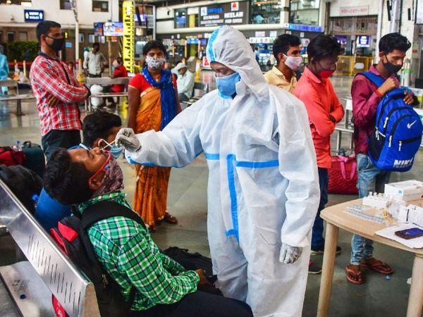 મુંબઈમાં એક રેલ્વે સ્ટેશન પર પહોંચેલા મુસાફરોની તપાસ કરતા BMCના આરોગ્ય કર્મચારી.
