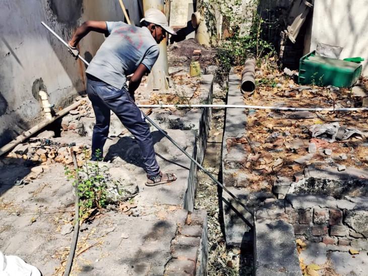 લાકડીના સહારે અસ્થિઓ વહાવતો ઉમરા સ્મશાનગૃહનો  કર્મચારી. - Divya Bhaskar