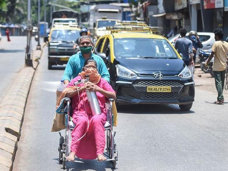 મુંબઈની એક વ્યક્તિ એની પત્નીને વ્હિસચેર પર હોસ્પિટલ લઈ જઈ રહી છે.