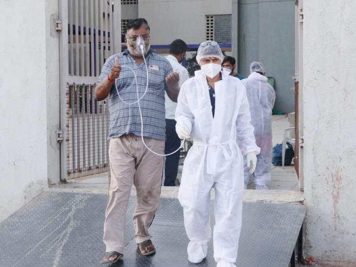 દર્દીને લઈ જતા સ્ટાફ પર્સનની તસવીર - Divya Bhaskar