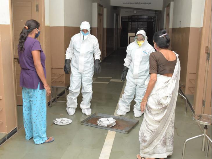 સલામતી માટે PPE કીટ પહેરીને ડિસ્પોઝેબલ ફૂડ પેકેટ કેન્દ્રની બહાર મૂકેલા ટેબલ સુધી પહોંચાડે છે