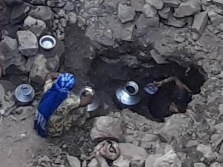 ખાડામાં ઉતરી બે બેડાં પાણી ભરવા મથતી મહિલાઓની તસવીર