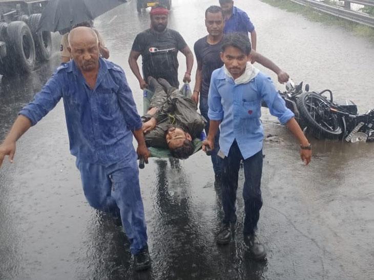 અકસ્માતમાં ગંભીર રીતે ઘવાયેલા યુવાનને હોસ્પિટલ લઇ જતા ટોલ પ્લાઝાના કર્મચારીઓ અને મૃતકની બાઇક. - Divya Bhaskar