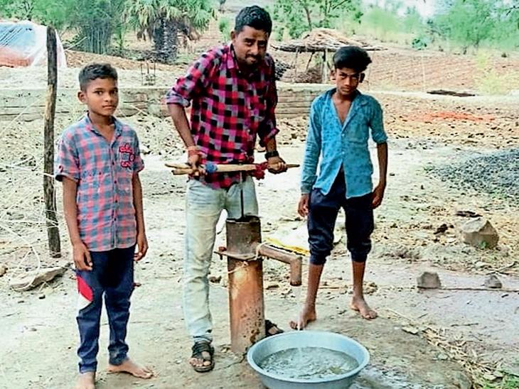 કુકરદા ગામે આંબા ફળીયાના હેન્ડપંપ ઉપર લાકડી બાંધી પાણી કાઢતા ગ્રામજનોની તસવીર. - Divya Bhaskar