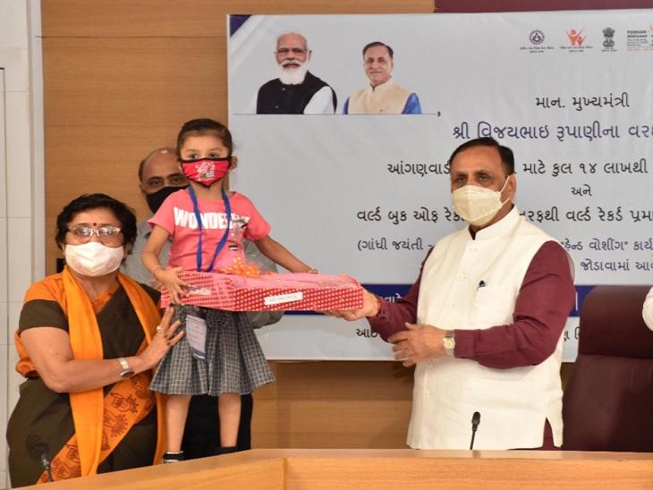 બાળકને યુનિફોર્મનું વિતરણ કરી રહેલા મુખ્યમંત્રી વિજય રૂપાણી - Divya Bhaskar
