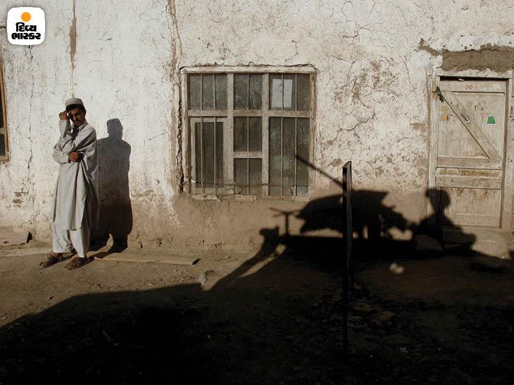 ઓગસ્ટ 2005: પાકિસ્તાનની સરહદથી નજીક આવેલા પકતિકા પ્રાંતમાં અમેરિકાના સૈન્યવાહનના પડછાયા પાસે ઊભેલો એક અફઘાની નાગરિક ફોટો: સ્કોટ એલ્સ