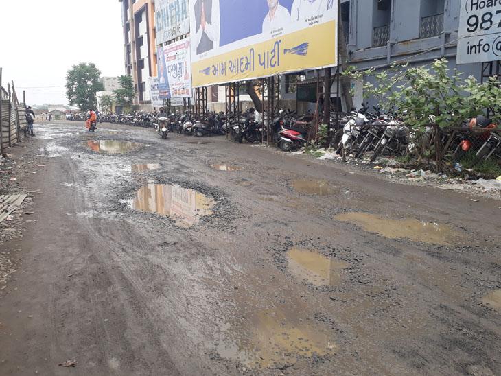 સુરેન્દ્રનગર શહેરના બસ સ્ટેશનમાં મુખ્ય ગેટ આગળ વરસાદી પાણી અને ખાડાઓના કારણે મુસાફરો હાલાકીનો સામનો કરી રહ્યાં છે. - Divya Bhaskar