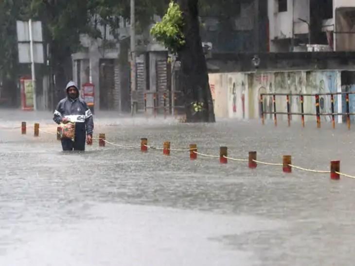ભારે વરસાદ વચ્ચે મુંબઇના સાયન વિસ્તારમાં બજારમાંથી સામાન લઈ જતો એક વ્યક્તિ