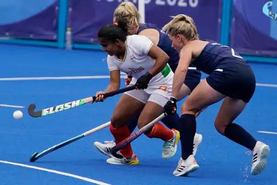 ભારતીય મહિલા હોકી ખેલાડી નેહા આયર્લેન્ડની ડિફેન્ડર્સને પછાડવાના પ્રયાસમાં.