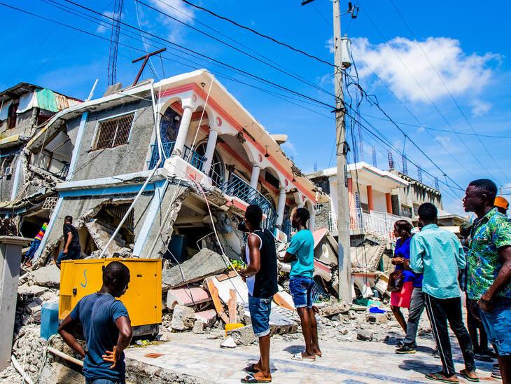 તૂટેલા મકાનને જોઈ રહેલા લોકો