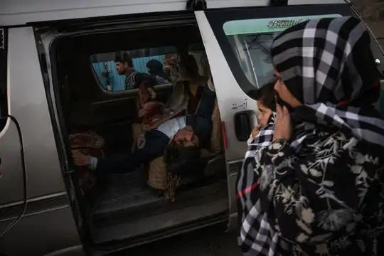 કારમાં લઈ જતા એક ઘાયલને જોઈ રહેલી એક મહિલા અને બાળક. આ હુમલામાં અનેક લોકો ગંભીર રીતે ઇજાગ્રસ્ત થયા છે.