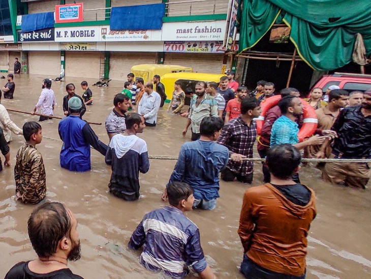 જામનગરના રસ્તા પર ભરાયેલા પાણી વચ્ચે બચાવકાર્ય - Divya Bhaskar