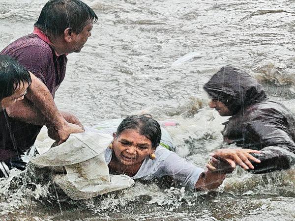રાજકોટમાં પાણીમાં ફસાયેલી મહિલાને બચાવી રહેલા સ્થાનિક લોકો. લોધિકામાં સૌથી વધુ 21 ઇંચ વરસાદ પડ્યો હતો. - Divya Bhaskar