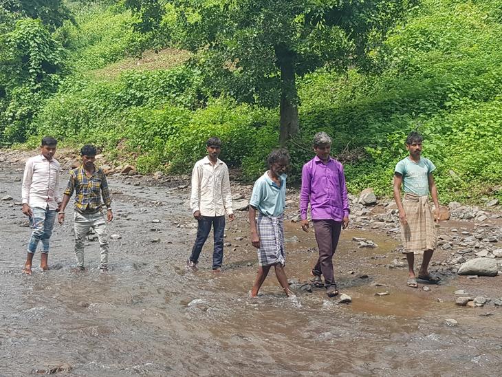 સાંકડીબારીના ગ્રામજનો પાણી ભરેલી કોતરો પાર કરી બેન્કના કામે આવે છે. - Divya Bhaskar