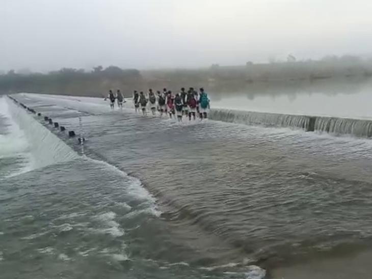 ગોઠણ સમા પાણીમાં વિદ્યાર્થિનીઓ કોઝવે પસાર કરી રહી છે.