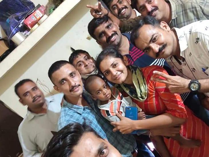 મુક્ત કરાયેલી બાળકી સાથે પોલીસ ટીમ - Divya Bhaskar